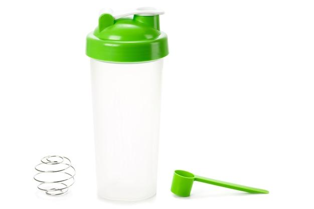 Grüner protein-shaker und schaufel isoliert auf weiß
