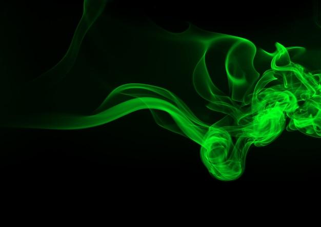 Grüner rauchauszug auf schwarzem hintergrund. dunkelheitskonzept