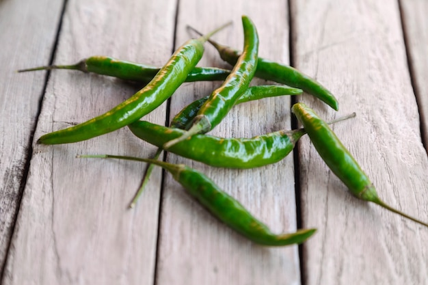 Grüner roher chili auf holztisch