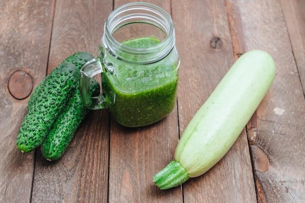 Grüner roher smoothie in einem einmachglas und grünem gemüse auf holzbrettern. gurken und zucchini stillleben