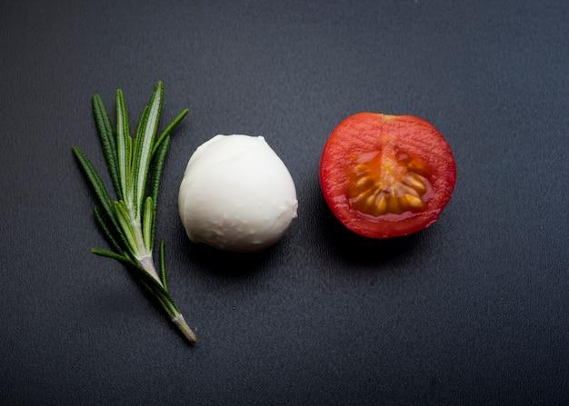 Grüner rosmarin; halber fröhlicher tomaten- und mozzarella-käse über schwarzer oberfläche