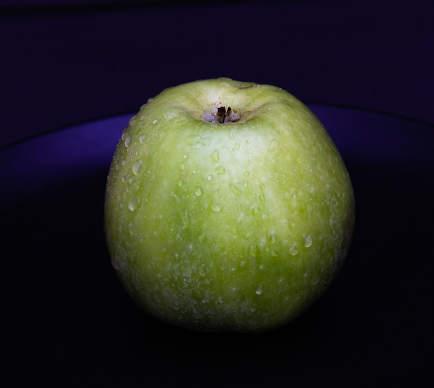 Grüner saftiger apfel mit wasser fällt auf schwarzblech auf dunklem hintergrund.
