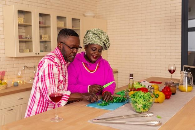 Grüner salat. angenehme afrikanische frau, die in der küche steht, während gemüse mit einem messer schneidet