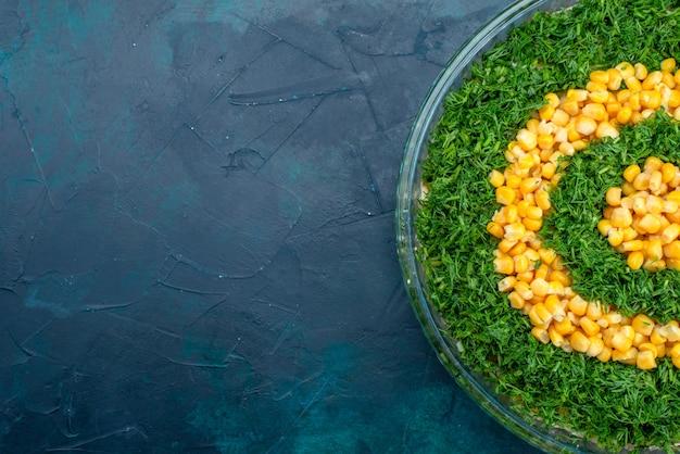 Grüner salat der draufsicht mit körnern innerhalb der runden glasplatte auf dem dunkelblauen schreibtisch.