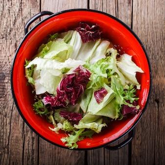 Grüner salat des sommers in einem roten sieb. capriccio.