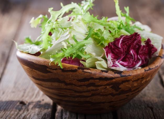 Grüner salat des sommers in einer hölzernen schüssel.