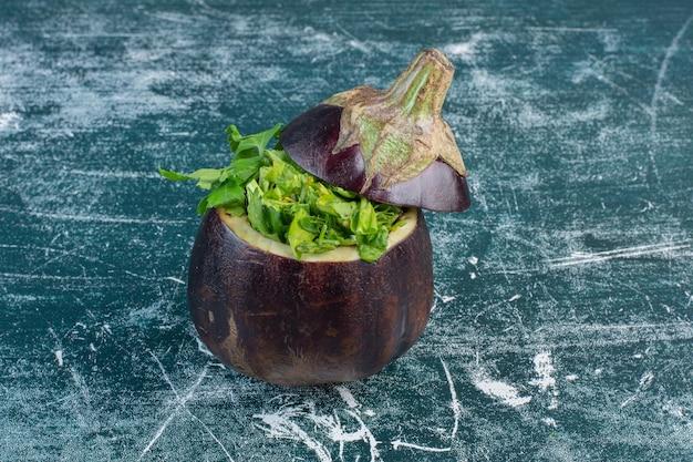 Grüner salat in der geschnitzten aubergine.