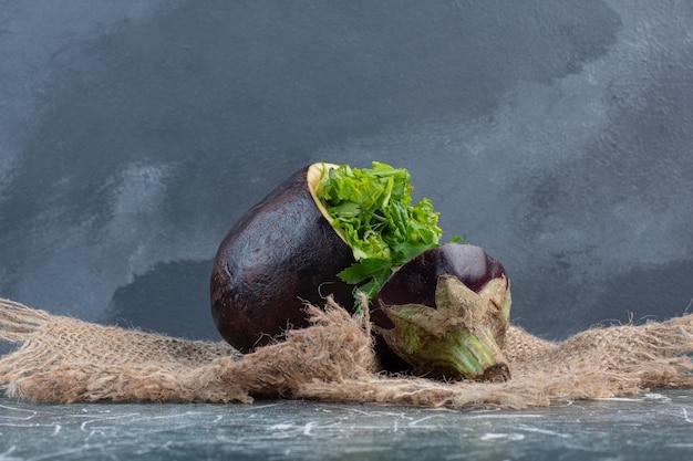 Grüner salat in einer geschnitzten lila aubergine.
