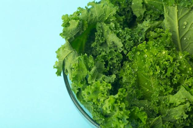 Grüner salat in einer glasschüssel auf blau