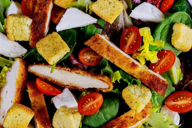 Grüner salat mit gegrilltem huhn mit tomaten, rucola und brot