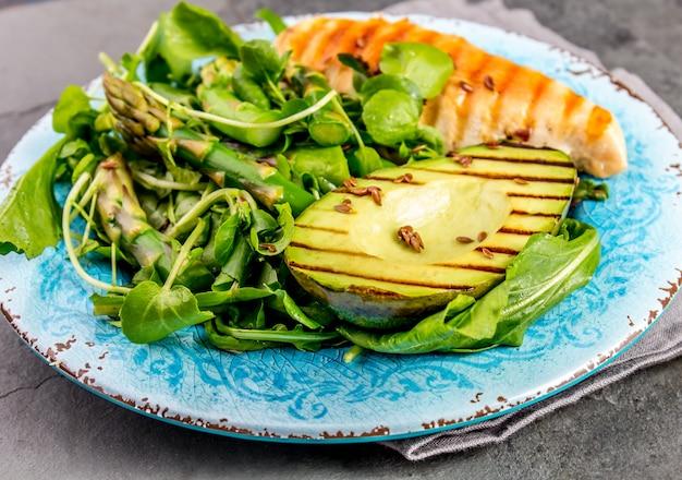 Grüner salat mit gegrillter avicado und gegrilltem huhn