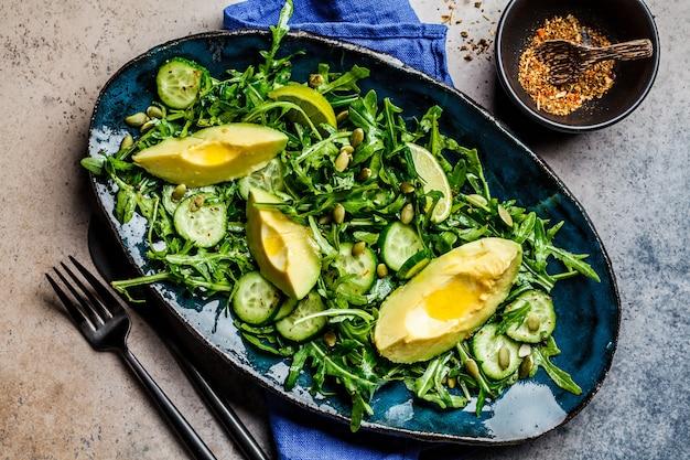 Grüner salat mit gurke, avocado und rucola in der blauen schale, dunkler hintergrund. draufsicht.