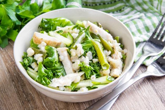 Grüner salat mit hühnchen, graupen, frischer gurke, grünen bohnen, gesundem, herzhaftem mittagessen