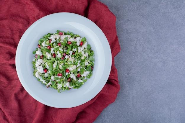 Grüner salat mit kräutern, blumenkohl und granatapfelkernen