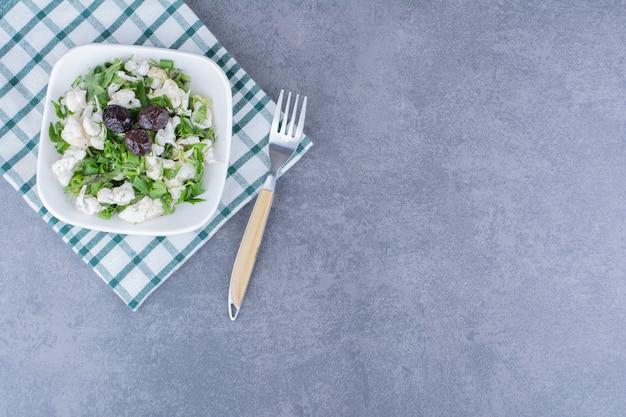 Grüner salat mit kräutern und blumenkohl in einer keramikschale