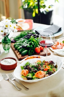 Grüner salat mit kräutern und einem glas rotwein.