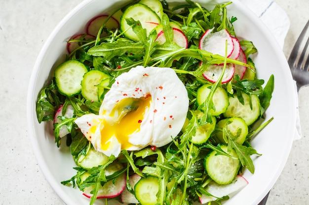 Grüner salat mit poschiertem ei, gurke und rettich in der weißen schüssel. gesundes lebensmittelkonzept.