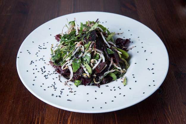 Grüner salat mit rote-bete-wurzeln auf einer ronde
