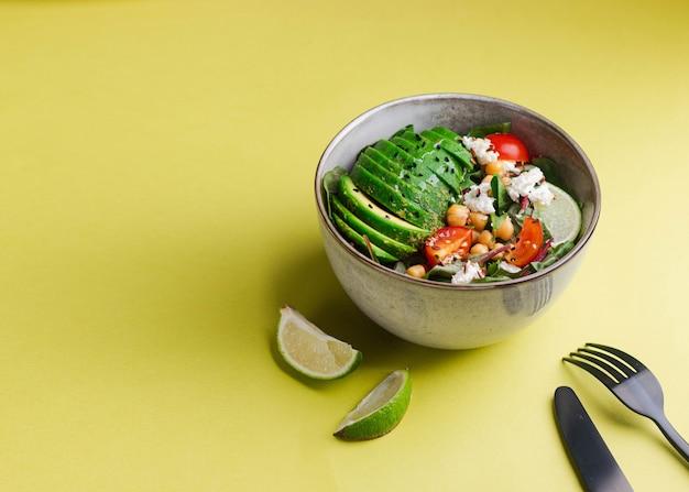 Grüner salat mit rucola, avocado, kichererbsen, kümmel, mangold, tomate, limette, hüttenkäse, leinsamen und sesam, olivenöl auf gelber wand. draufsicht mit copyspace. banner. gesunde eati