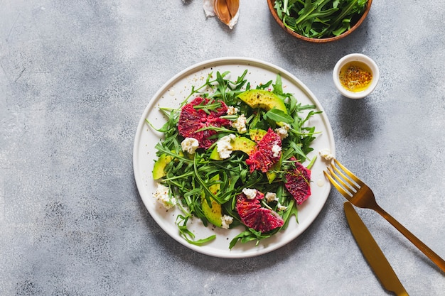 Grüner salat mit rucola, blutorange, avocado, hüttenkäse auf blauer steinmauer mit schwarzer gabel und messer. konzept für gesunde ernährung. flatlay mit copyspace