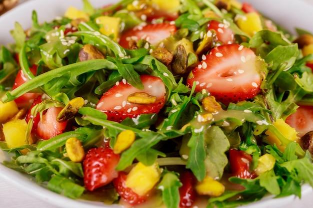 Grüner salat mit rucola, erdbeeren, mango und pistazien