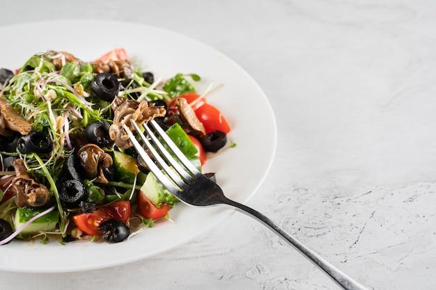 Grüner salat mit schneckentraubenschnecken auf weißem hintergrund. französische gourmetküche.