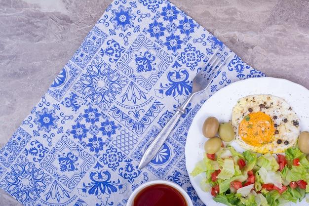 Grüner salat mit spiegelei und einer tasse tee