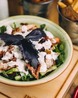 Grüner salat mit weißkäsewürfeln, crackern und roten basilikumblättern innerhalb der grünen schüssel.