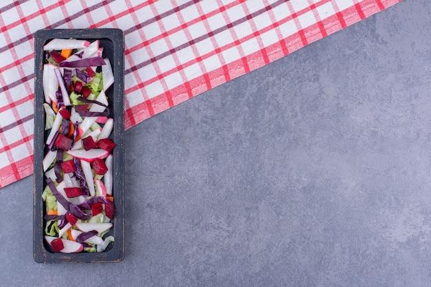 Grüner salat mit zutaten in einer schwarzen platte.