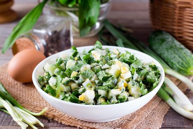 Grüner salat mit zwiebel und ei auf einem tisch