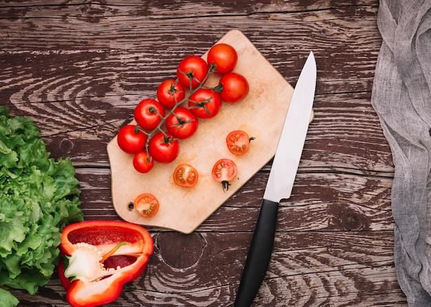 Grüner salat; paprika- und kirschtomaten auf schneidebrett mit messer über dem holzschreibtisch