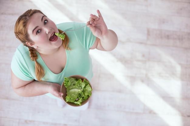 Grüner salat. starke rothaarige frau, die schüssel hält, während sie ihren salat isst