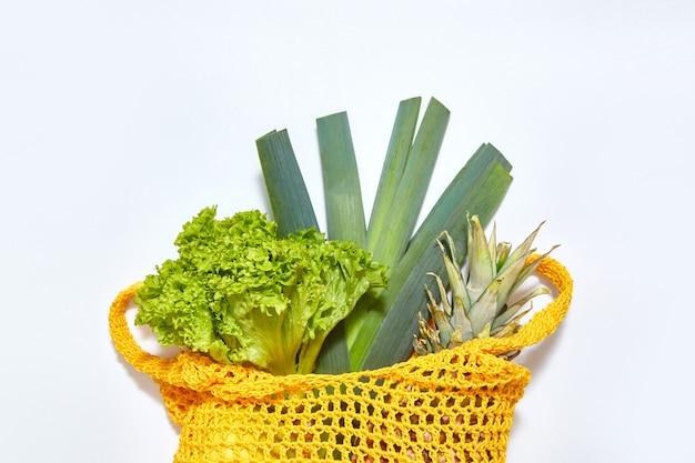 Grüner salat und früchte in gelbem öko-string-beutel auf weißem hintergrund. der blick von oben. flach mit kopierraum liegen.
