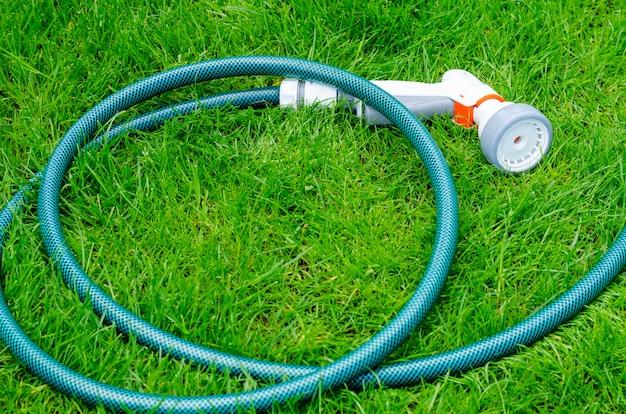 Grüner schlauch für die bewässerung liegt auf gras, rasen