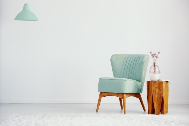 Grüner sessel neben holztisch mit pflanze im loft-interieur mit kopierraum und lampe. echtes foto