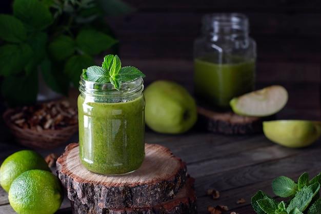 Grüner smoothie aus grünem bio-apfel, minze und spinat auf holzhintergrund. mit kopierplatz