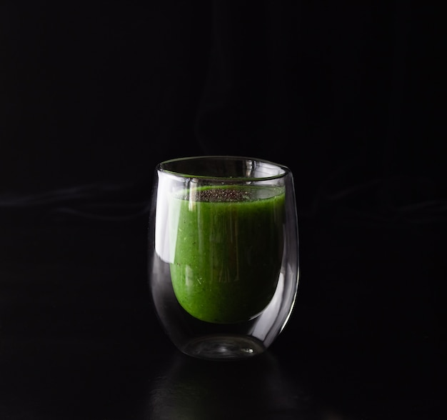 Grüner smoothie in einem glasglas auf schwarzem hintergrund. gesundes essen kochen.