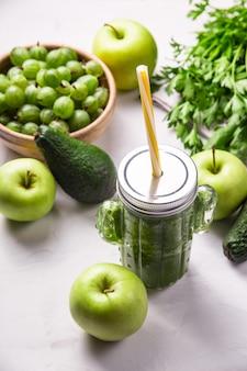 Grüner smoothie in einem kaktusförmigen glas unter den grünen bestandteilen