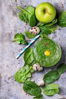 Grüner smoothie mit apfel und blättern auf beton