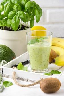 Grüner smoothie mit banane, kiwi, basilikum und avocado