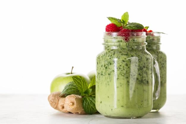 Grüner smoothie mit erdbeeren im glas
