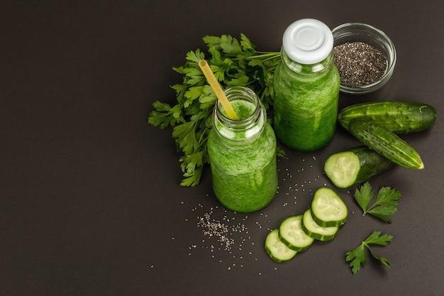 Grüner smoothie mit gurke in glasflaschen. frisches reifes gemüse, gemüse und chiasamen. betonhintergrund aus schwarzem stein, ansicht von oben
