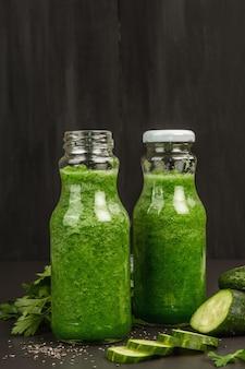 Grüner smoothie mit gurke in glasflaschen. frisches reifes gemüse, gemüse und chiasamen. schwarzer steinbeton hintergrund, nahaufnahme