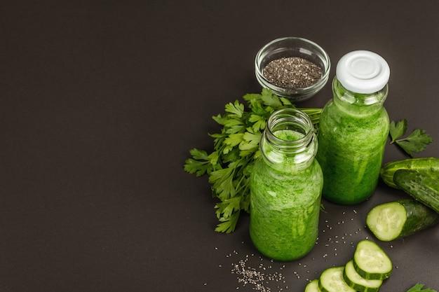 Grüner smoothie mit gurke in glasflaschen. frisches reifes gemüse, gemüse und chiasamen. schwarzer steinbetonhintergrund, kopienraum