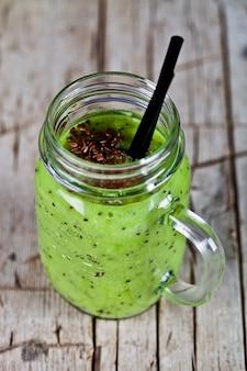 Grüner smoothie mit kiwi-, apfel-, limetten- und leinensamen.