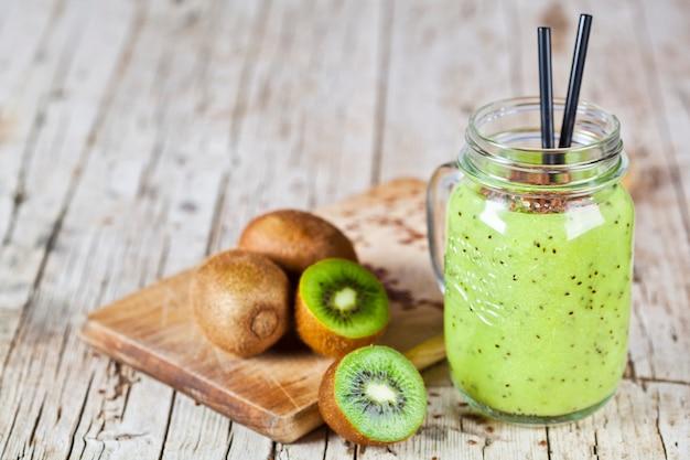 Grüner smoothie mit kiwi-, apfel-, zitronen- und leinensamen.