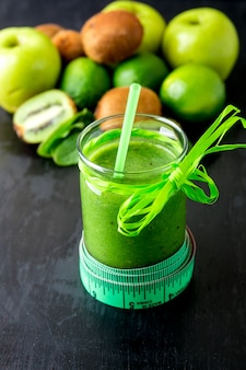 Grüner smoothie nahe zentimeter und bestandteile für ihn auf schwarzer holzoberfläche