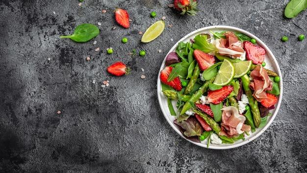Grüner spargel, erdbeere, rucola und hüttenkäsesalat