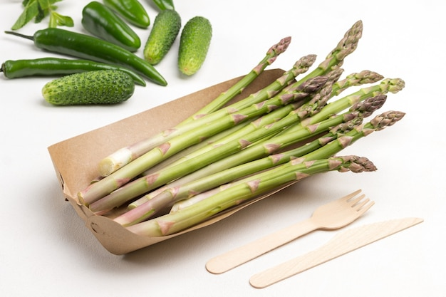 Grüner spargel in einwegschale aus pappe. gurken, grüne paprika auf dem tisch. weißer hintergrund. ansicht von oben.
