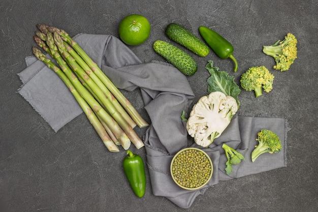 Grüner spargel, mungobohne und blumenkohl auf grauer serviette. paprika, gurken auf dem tisch. schwarzer hintergrund. flach legen
